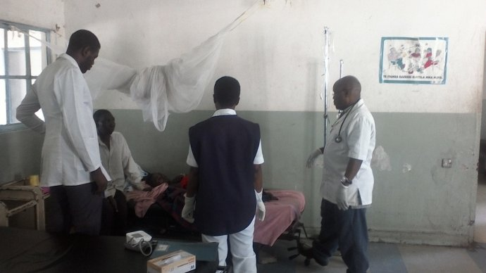 Photo: Dr Fayulu (right) and Male ward team discuss the case of a severe malaria patient.
