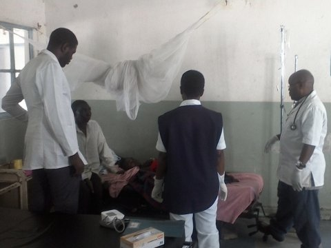 Dr Fayulu (right) and Male ward team discuss the case of a severe malaria patient.
